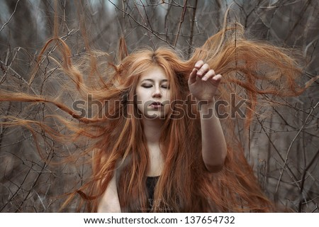 mysterious red-haired girl in the woods - stock photo