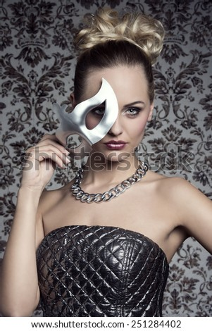 mysterious sensual blonde woman with silver creative dress and elegant hair-style covering her face with mask in carnival shoot  - stock photo