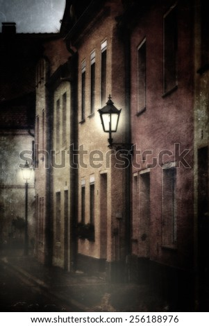Mysterious street scene with luminous lanterns in the dark. Photo with textures to achieve a mystical, mysterious impression. - stock photo