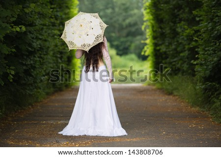 Mysterious woman departing off into the distance - stock photo