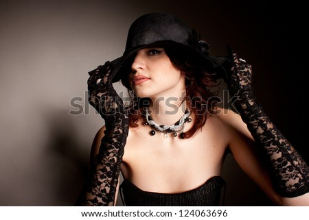 mysterious woman dressed in a black hat and lace gloves