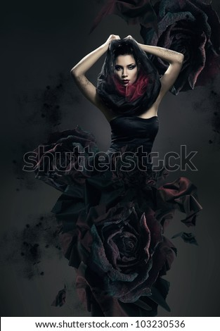 mysterious woman in dark hood and rose dress - stock photo
