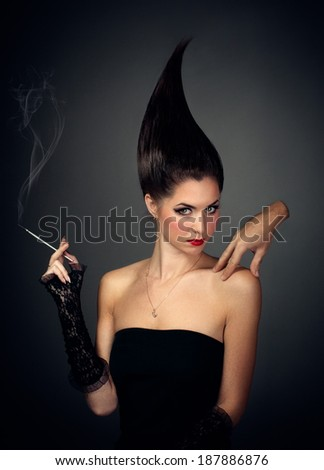 mysterious woman in dark hood with cigarette - stock photo