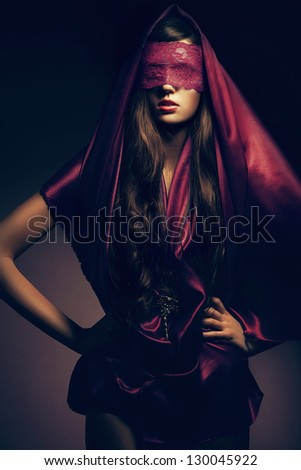 mysterious woman in red cape - stock photo
