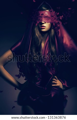 mysterious woman in red cape with leaves - stock photo