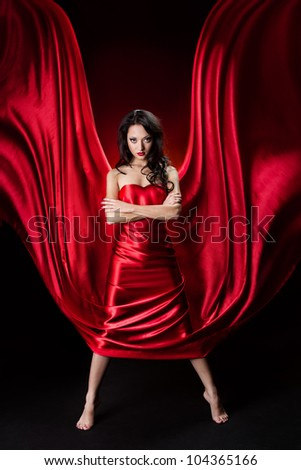 Mysterious  woman in red dress waving as wings over black background.