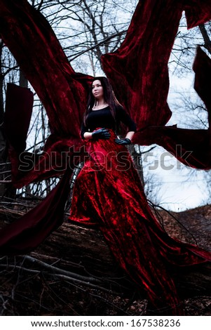 Mysterious woman or witch in long red dress standing in dark forest with flying fabric - stock photo