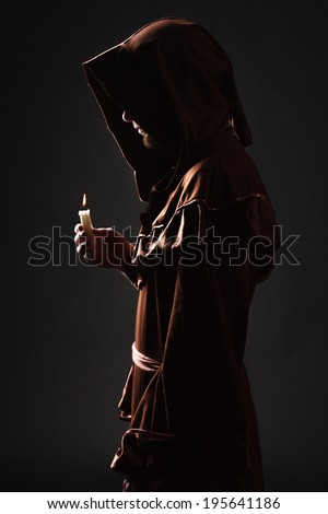 Mystery monk praying on kneels in dark - stock photo