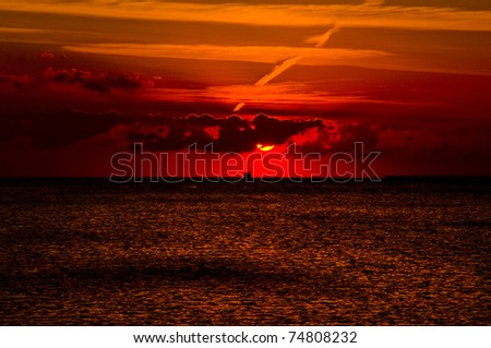 mystery sunset over  Red sea. Sun, colorful sky and clouds over dark sea