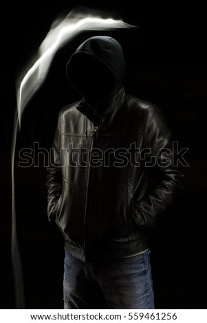 Mystic black hooded man standing in the darkness. Evil spirit.