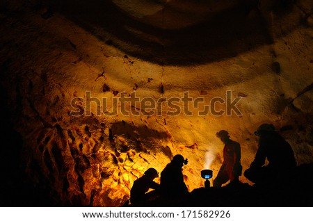 Mystic cave. A group of explorers resting in a cave - stock photo