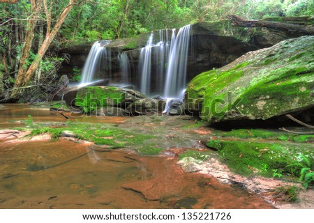 mystic serene flowing tropical rainforest waterfall Somersby Falls , Gosford, New South Wales, Australia - stock photo