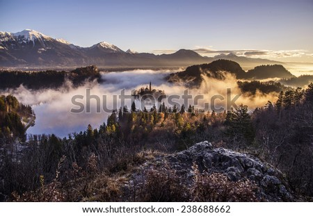 Mystical Sunrise over Lake in the Mountains. Mist is over the lake covering the church almost in full. Castle and surrounding Mountains are basking in the sun. Scenic and atmospheric sunrise on Bled. - stock photo