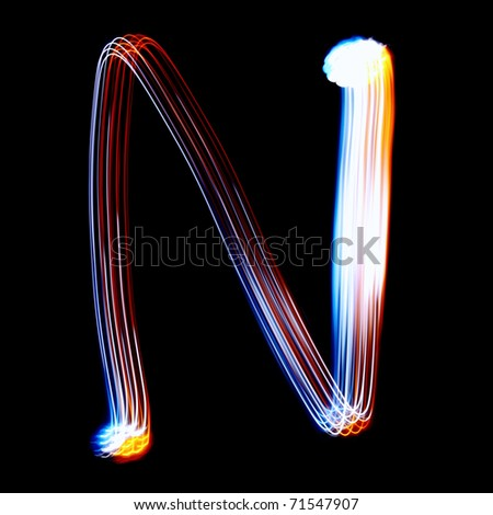 N - Created by light colorful letters over black background - stock photo