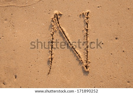 N text written in the sandy on the beach - stock photo