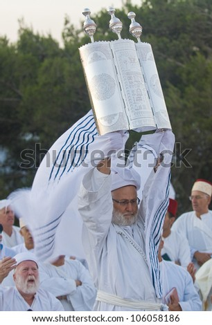 NABLUS, WEST BANK - JUNE 24 : A priest of the ancient Samaritan community holds up a Torah scroll during the holy day of Shavuot in Mount Gerizim on June 24 2012