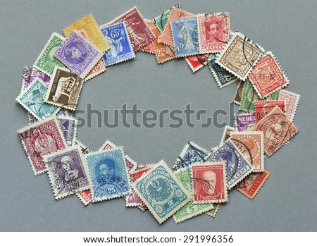 NACHOD, CZECH REPUBLIC - JUNE 6, 2015: Philately - heap of European vintage postage stamps as oval frame on grey cardboard - stock photo