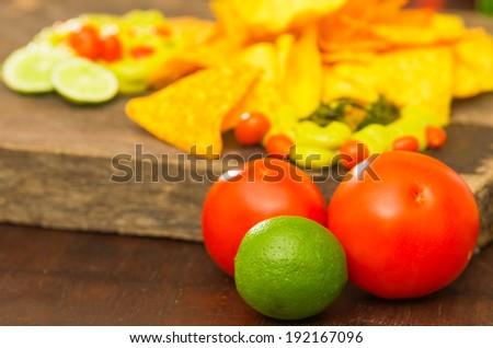 nachos and guacamole dip, avocado, lemon and tomato close up - stock photo