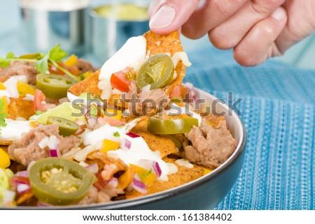 Nachos - Cheesy nachos topped with sour cream, refried beans, pico de gallo, jalapenos and guacamole. - stock photo