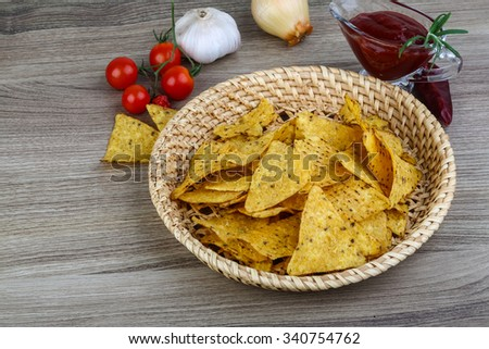Nachos chips with tomato hot sauce on the wood background