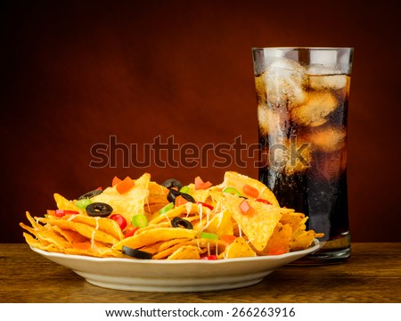 nachos on a plate served with a glass of cold cola drink