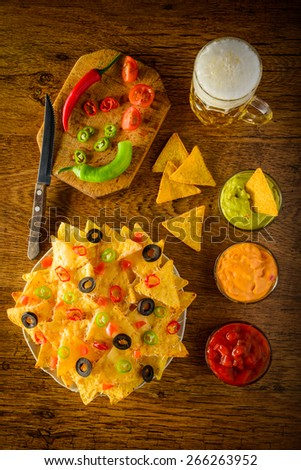 nachos on a plate with salsa, cheese and guacamole dip and beer mug - stock photo