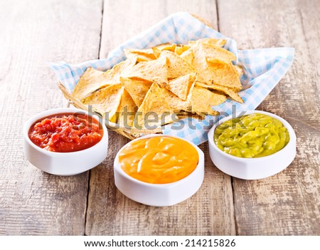 nachos with various sauces on wooden table - stock photo