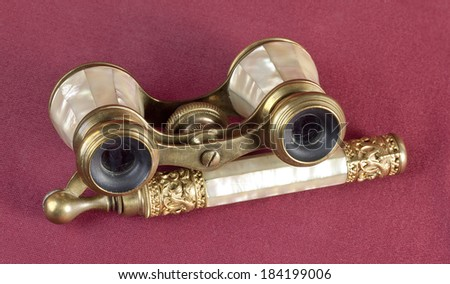 Nacre and brass opera glasses on oxblood red background - stock photo