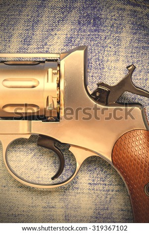 Nagan revolver on blue jeans background, close-up, part of. instagram image filter retro style