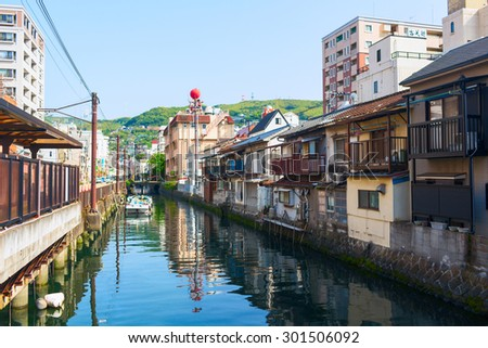 NAGASAKI CITY, JAPAN - 19 MAY 2013: Old Town district in Nagasaki City. Artificial canal flows into the Japanese Sea. Nagasaki, Japan. - stock photo