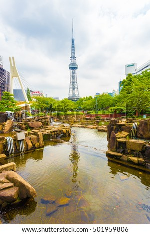 Nagoya, Japan - July 3, 2015: View over pond and rock garden at Hisaya Odori Park in city center with Nagoya TV Tower in background on cloudy overcast day
