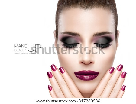 Nail art and Makeup concept. Beautiful fashion model woman with perfect skin. Trendy burgundy lips, nails and smoky eyes. Fashionable eyelashes. High fashion portrait on white with sample text - stock photo