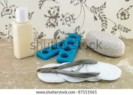 Nail care concept with foot cream, pumice stone, toe separator, cotton pads. - stock photo