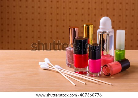 Nail polish bottles and cotton bud on wooden table - stock photo