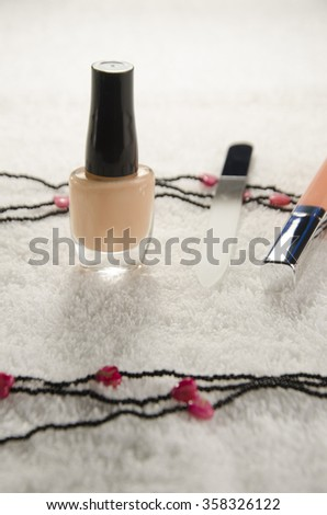 nail polish, file and lip gloss on white cotton towel