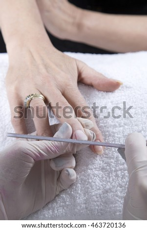 Nail Treatment - Manicurist Filing Fingernails With Nail File, Making A Perfect Nail Form On White Towel Closeup