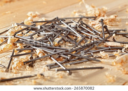Nails and wooden shavings on the workbench - stock photo