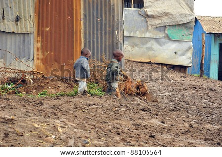 NAIROBI, KENYA  OCT. 13: Unidentified children walk in mud  through the Nairobi slum Oct. 13 2011 in Nairobi, Kenya. Kibera is the largest slum in Nairobi, and the second largest urban slum in Africa - stock photo