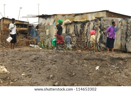 NAIROBI, KENYA-OCT. 13: Unidentified people walk in mud through the Nairobi slum Oct. 13 2011 in Nairobi, Kenya. Kibera is the largest slum in Nairobi, and the second largest urban slum in Africa - stock photo