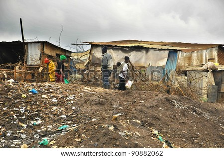 NAIROBI, KENYA OCT. 13: Unidentified people walk in mud through the Nairobi slum Oct. 13 2011 in Nairobi, Kenya. Kibera is the largest slum in Nairobi, and the second largest urban slum in Africa - stock photo