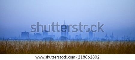 nairobi skyline before dawn partially obscured by fog - stock photo