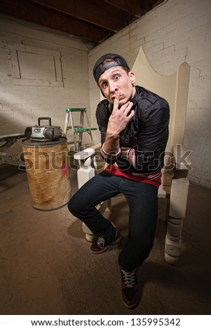 Naive young urban adult in throne with finger on lips - stock photo
