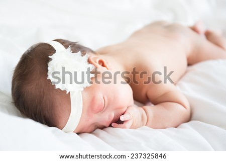 Naked asian infant baby lying on white bed background