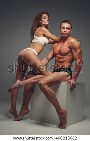 Naked athletic couple posing in studio. - stock photo