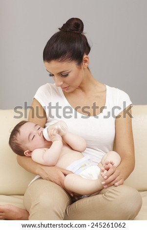 Naked baby fell asleep in mother's arms while drinking from feeding bottle. - stock photo