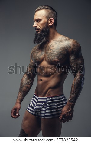 Naked bearded man with tattooed body standing on a grey background. - stock photo