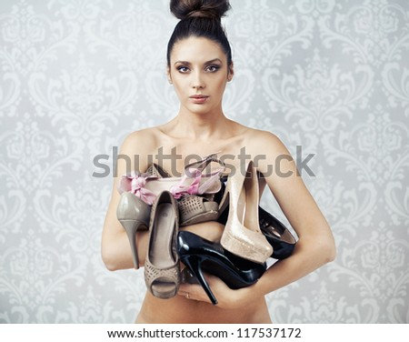 Naked beauty holding high heels - stock photo