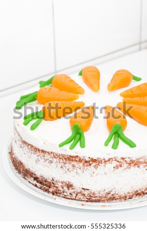 Naked carrot cake decorated with orange marzipan carrots on homogenous white background