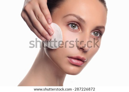 Naked girl with towel on head touches her body, isolated on white. Concept of health care, beauty and youth.Young beautiful woman - stock photo