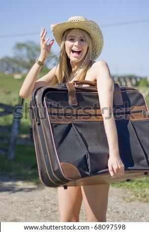 Naked Lady Vacationer Laughs In Rural Lifestyle Hat While Holding Her Suitcase As Her Clothes Were Lost In Transit - stock photo